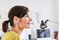 Side view of mature woman in office looking away smiling