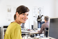 Side view of mature woman in office looking at camera smiling