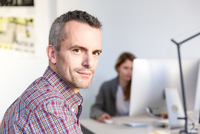 Side view of mature man in office looking at camera smiling