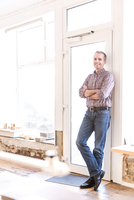 Full length view of mature man leaning against doorway arms folded looking at camera smiling