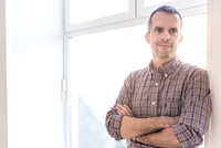 Mature man wearing check shirt leaning against window arms crossed looking away smiling