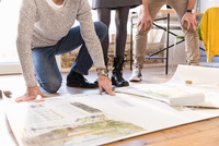 Low section of architects discussing blueprint on office floor