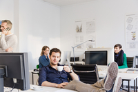 Mid adult man in office, feet on desk holding teacup looking at camera