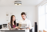 Architects in office holding architectural model