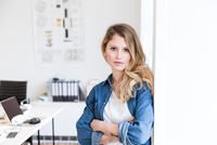 Young woman in office leaning against wall arms crossed looking at camera