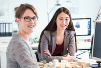 Women in office with architectural model looking at camera smiling