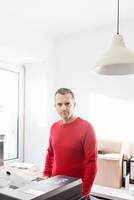 Mature man in office wearing red sweater looking at camera smiling