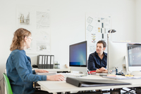 Colleagues sitting at desk in office using computers talking