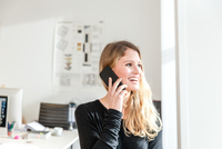 Young woman in office using smartphone to make telephone call looking away smiling