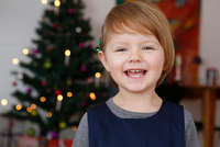 Portrait of girl in front of christmas tree smiling
