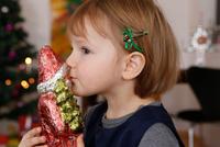 Side view of girl kissing christmas ornament of santa
