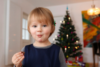 Girl in front of christmas tree eating chocolate looking at camera