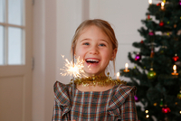 Girl in front of christmas tree holding sparkler looking at camera smiling