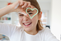 Girl looking through heart shaped cookie cutter smiling