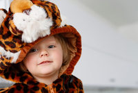 Girl dressed up in animal costume looking away smiling