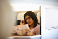 Mature businesswoman reading newspaper in airplane seat