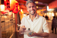 Man holding sushi with chopstick looking at camera laughing