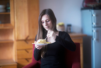 Young woman at home, eating lunch
