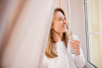 Mid adult woman drinking glass of water whilst looking through window