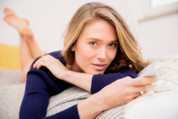 Portrait of woman lying on bed using smartphone