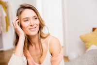 Woman sitting looking sideways from bed with hand on head