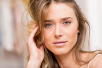 Close up portrait of beautiful woman with hand in long blond hair