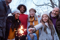 Girl with multi generation family holding sparkler smiling