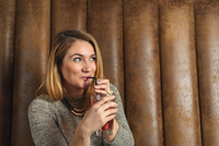 Mid adult woman in bar drinking cocktail looking away smiling