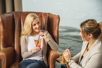 High angle view of mid adult women in bar sitting in leather armchairs face to face holding cocktails smiling