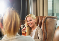 Mid adult woman in bar sitting in leather armchair holding cocktail smiling at friend