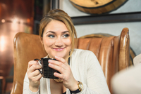 Mid adult woman sitting in leather armchair holding coffee cup looking away smiling