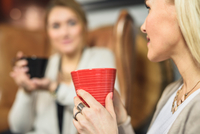 Cropped view of mid adult women face to face holding coffee cups smiling