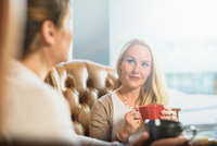 Mid adult woman sitting in leather armchair holding coffee cup looking at friend smiling