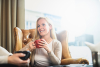 Mid adult woman sitting in leather armchair in front of window holding coffee cup looking at friend smiling