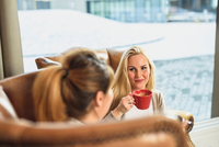 High angle view of mid adult woman sitting in leather armchair in front of window holding coffee cup looking at friend smiling