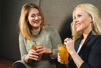 Mid adult women in public house holding cocktails smiling