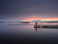Man standing on pier by lake looking at sunset, Thingvellir, Iceland
