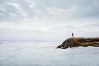 Woman standing by frozen lake, Holtsos, Iceland