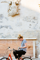 Young woman on bicycle writing in notebook, Ferrara, Italy