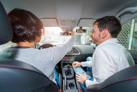 Male driving instructor with female student adjusting car mirror from driving seat