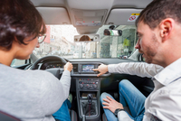 Male driving instructor pointing out sat nav to female student in driving seat