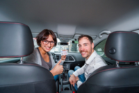 Portrait of male driving instructor and successful female student holding driving license in car