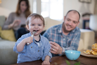 Baby boy feeding himself with spoon looking at camera smiling