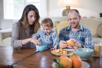Parents having lunch with baby boy, peeling orange