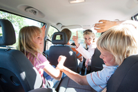 Children fighting in back seat of vehicle on road trip