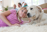 Girl and pet dog lying on carpet, family using laptop in background