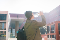Young urban man drinking from bottle of water
