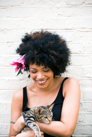 Portrait of woman with flower in hair, cat in arms