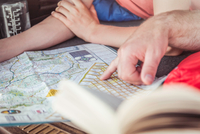 Close up man and teenage son hands pointing at map whilst lying in vehicle