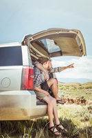 Mature man and teenage son pointing from off road vehicle, Bridger, Montana, USA